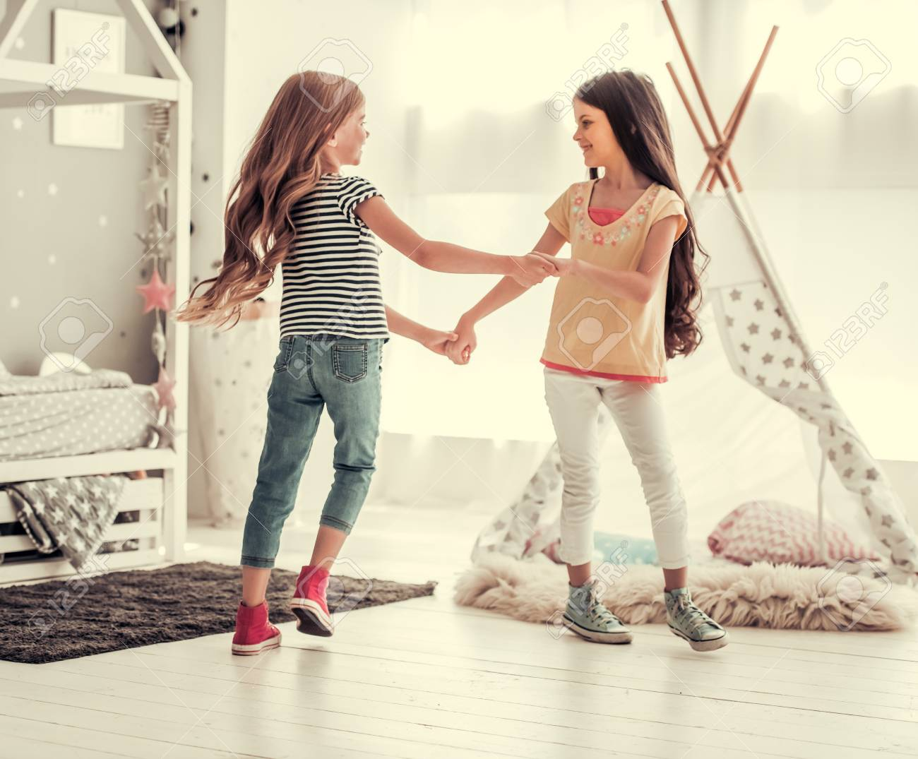 Two happy little girls are dancing and smiling while playing in children's room at home - 84680757