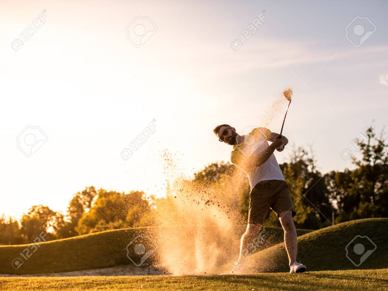 Handsome guy is using a golf club while playing golf, beautiful sun shining, splashed of sand - 85489125