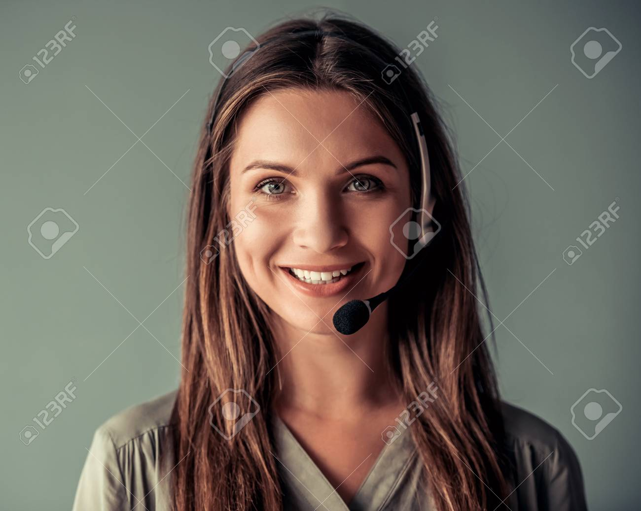 Beautiful business woman in headset is looking at camera and smiling, on gray background - 85476883