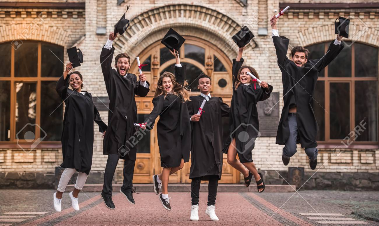 Successful graduates in academic dresses are holding diplomas, looking at camera and smiling while jumping for the photo outdoors - 88355323