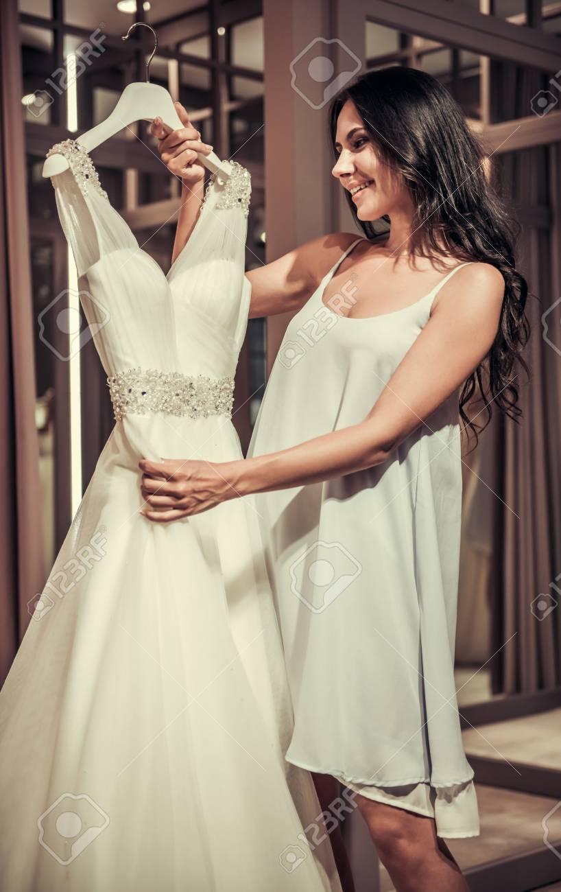 Bela Jovem Noiva Está Sorrindo Ao Escolher Elegantes Vestidos De Casamento No Salão De Casamento Moderno