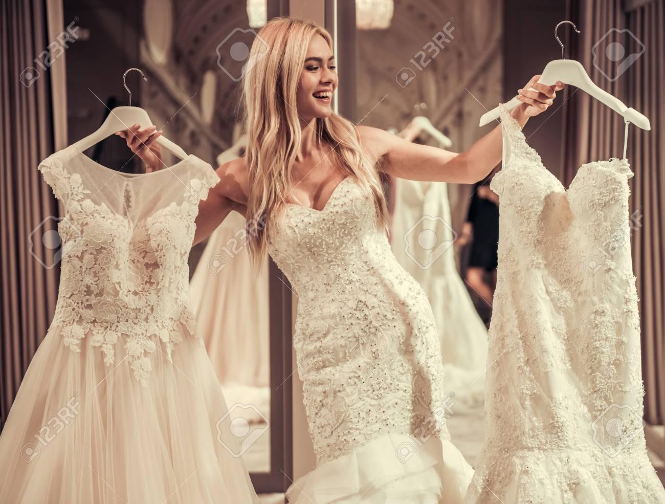 Atraente Jovem Noiva Está Sorrindo Ao Experimentar O Vestido De Casamento No Salão De Casamento Moderno