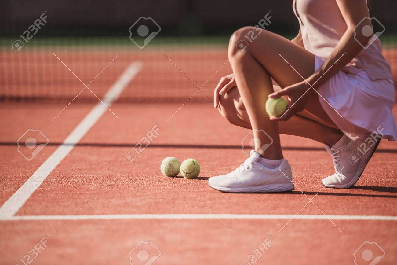 Cropped image of girl holding a tennis ball while playing tennis on court outdoors - 88858588