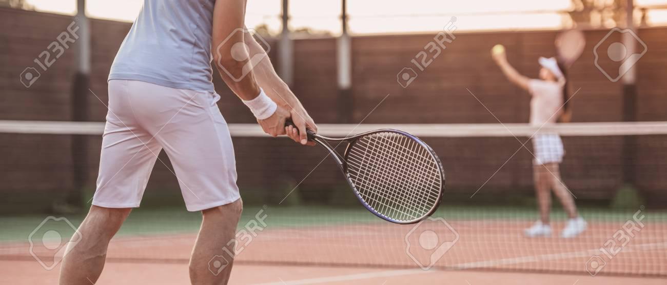3481021bc2 Foto de archivo - Hermosa mujer joven y guapo están jugando al tenis en la  cancha de tenis al aire libre