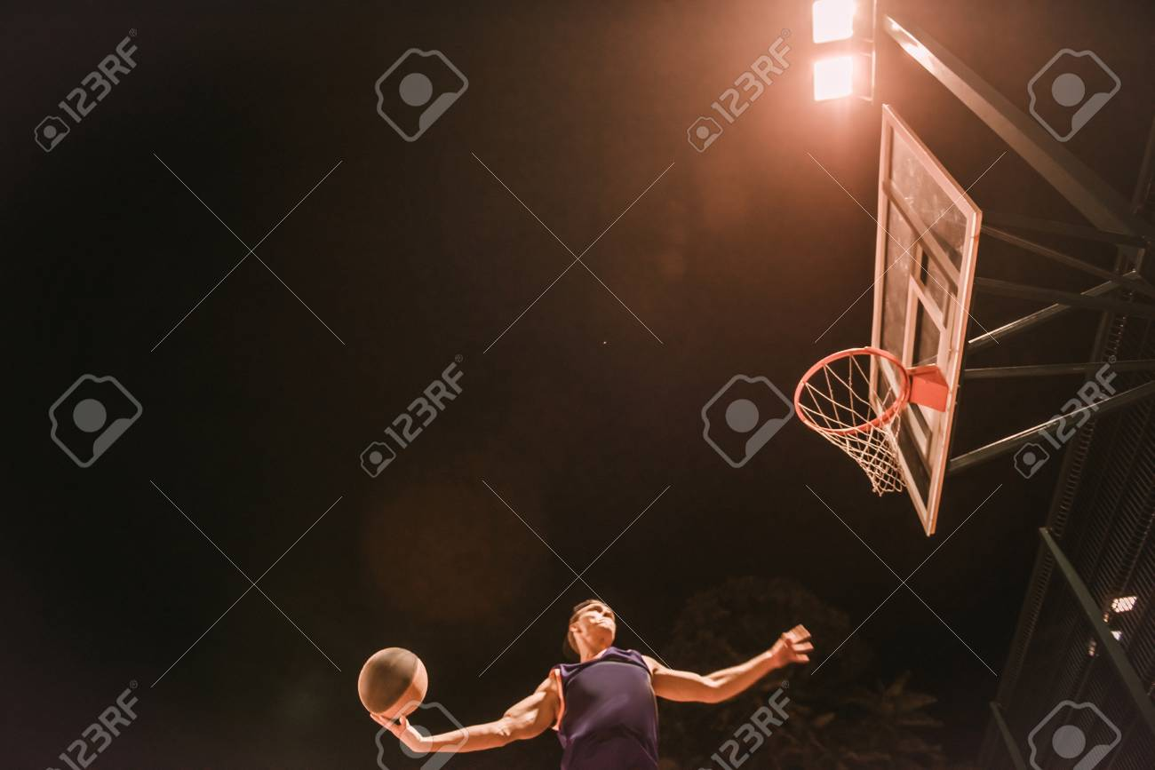 Stylish young basketball player in cap is jumping and shooting a ball through the hoop while playing outdoors at night - 89602170