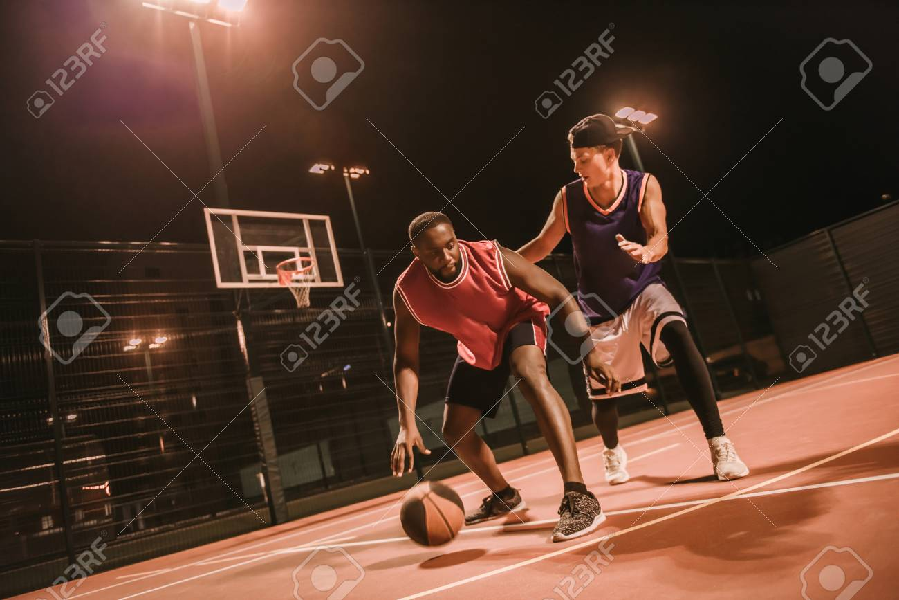 Handsome guys are playing basketball outdoors at night - 90372542