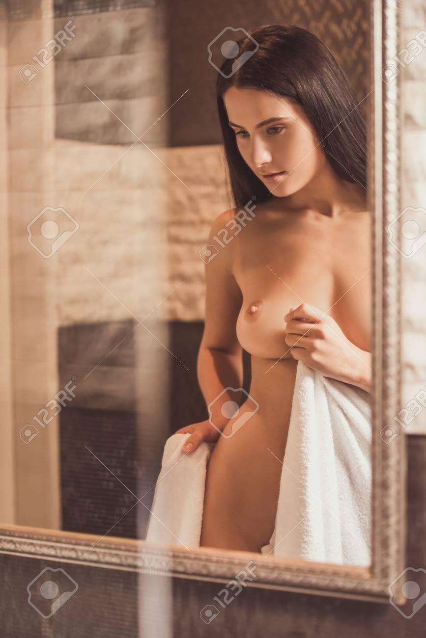 Joven Mujer Desnuda Limpiando Su Cuerpo Con Una Toalla Y Mirando Al Espejo En El Baño