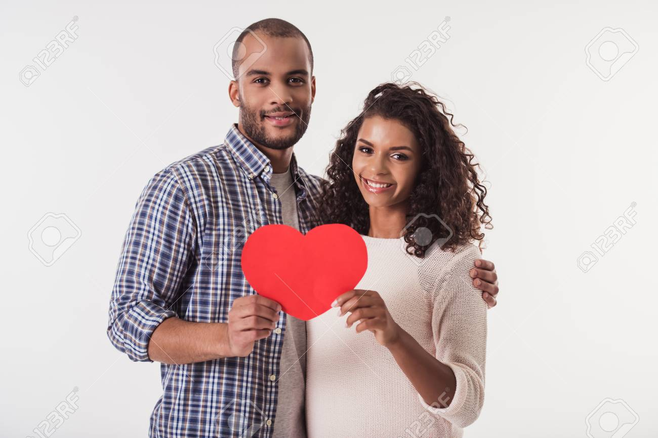 Beautiful Afro American couple holding a big red paper heart, looking at camera and smiling, isolated on white background - 89604185
