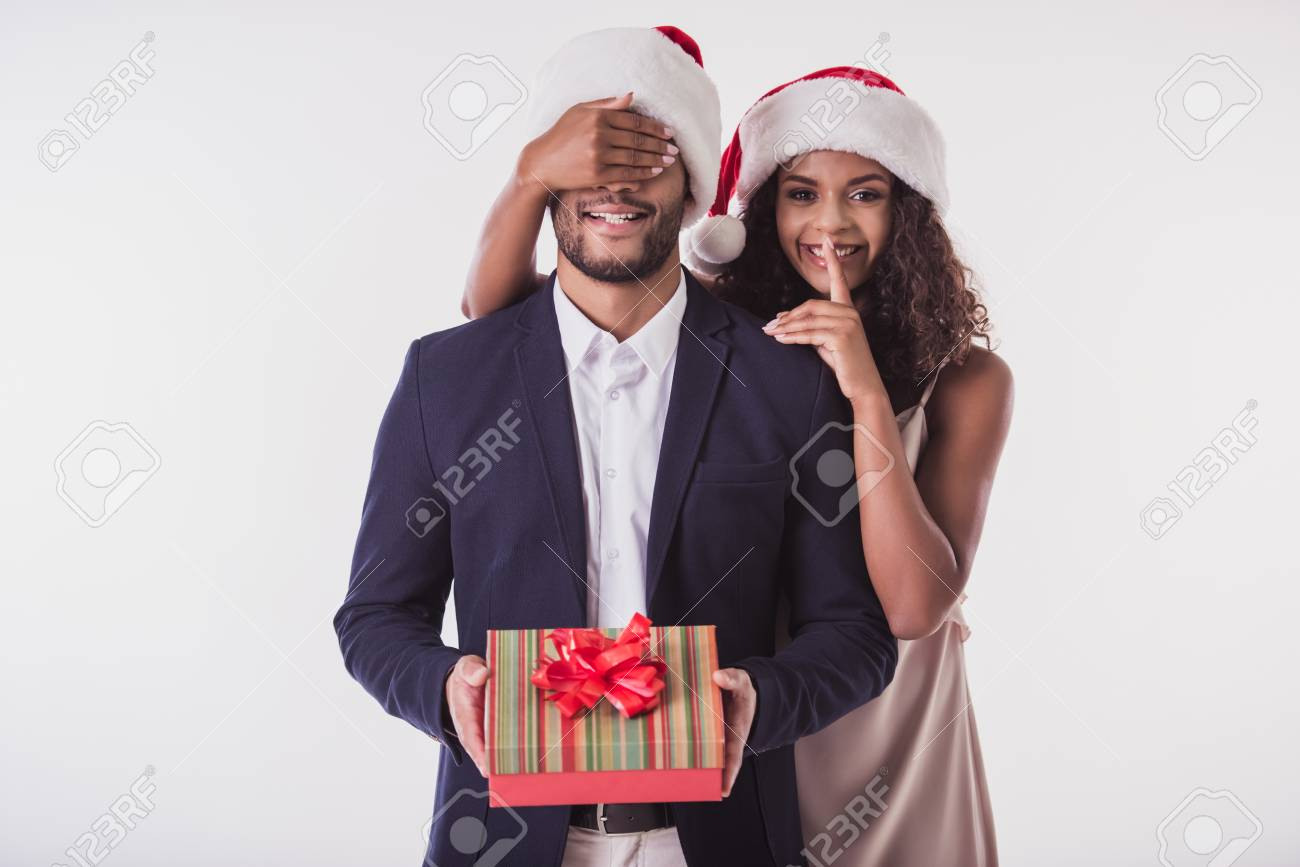 Elegant Afro American couple in Santa hats. Beautiful is covering her boyfriend's eyes, showing silence sign, looking at camera and smiling, isolated on white - 89665690