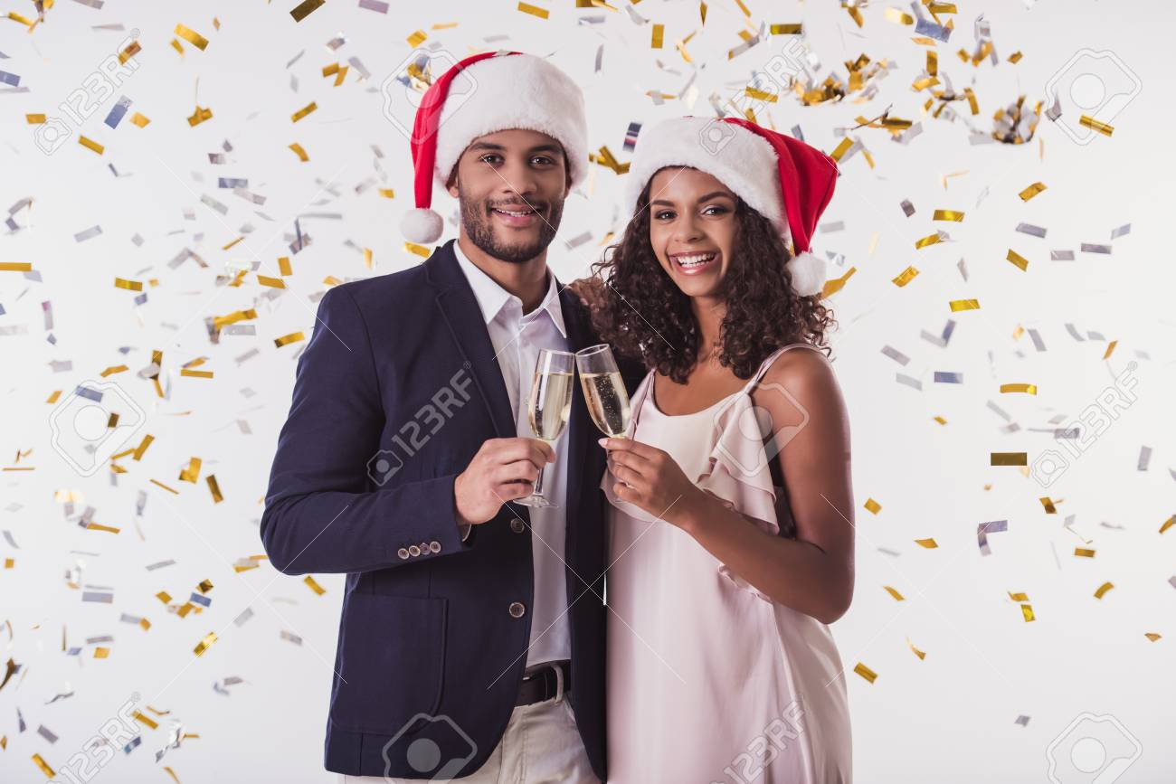 Elegant Afro American couple in Santa hats clinking glasses of champagne, looking at camera and smiling, on white background - 89604434