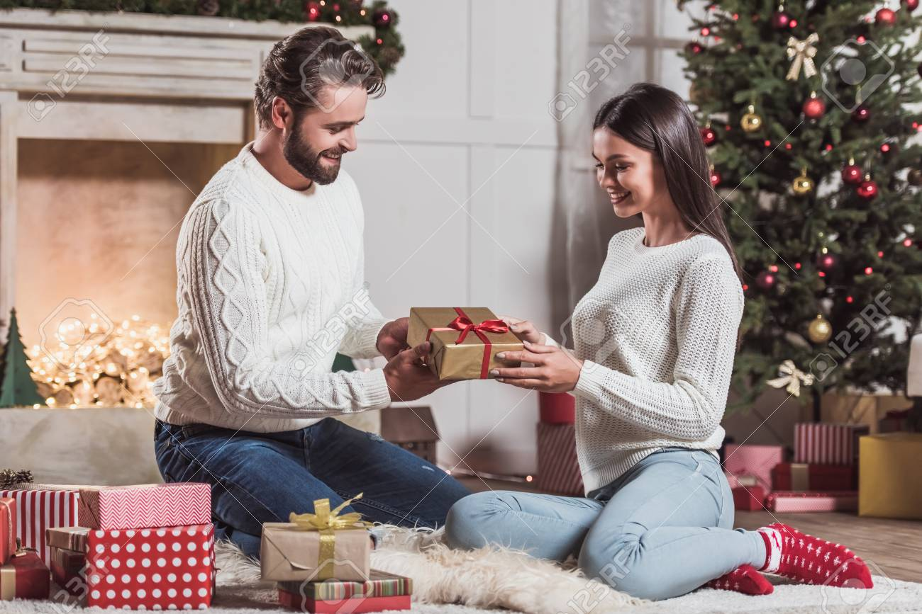 merry christmas and happy new year handsome man is giving his beautiful wife a christmas