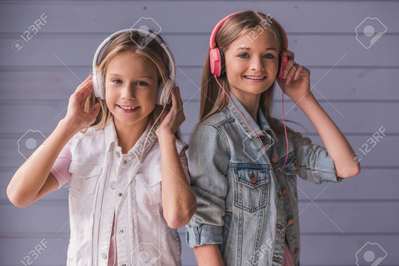 Two attractive teenage girls in headphones are listening to music, looking at camera and smiling, on gray wall background - 91795878