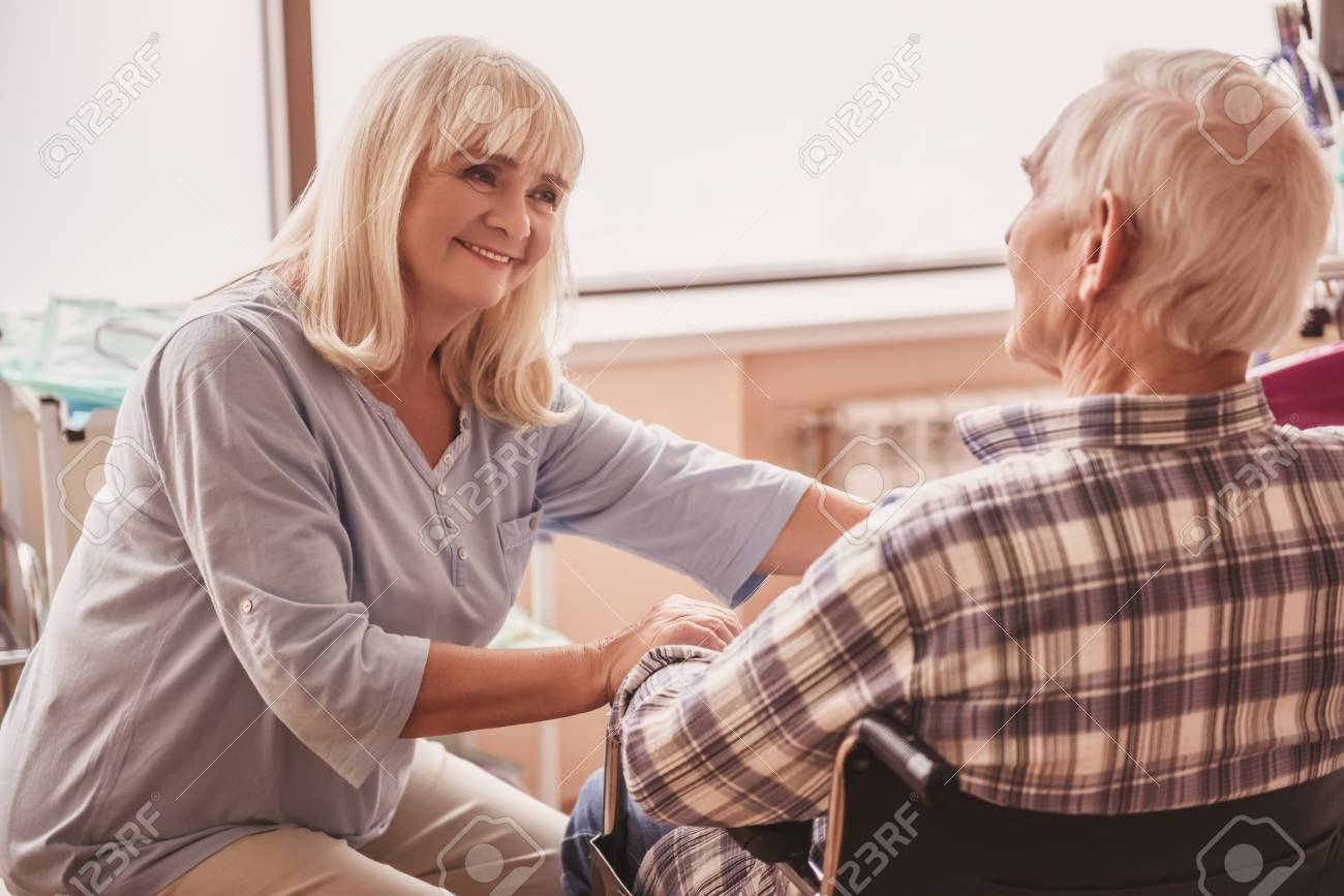 Beautiful old lady is talking to her husband and smiling while he is sitting in the wheelchair in hospital ward - 102322514