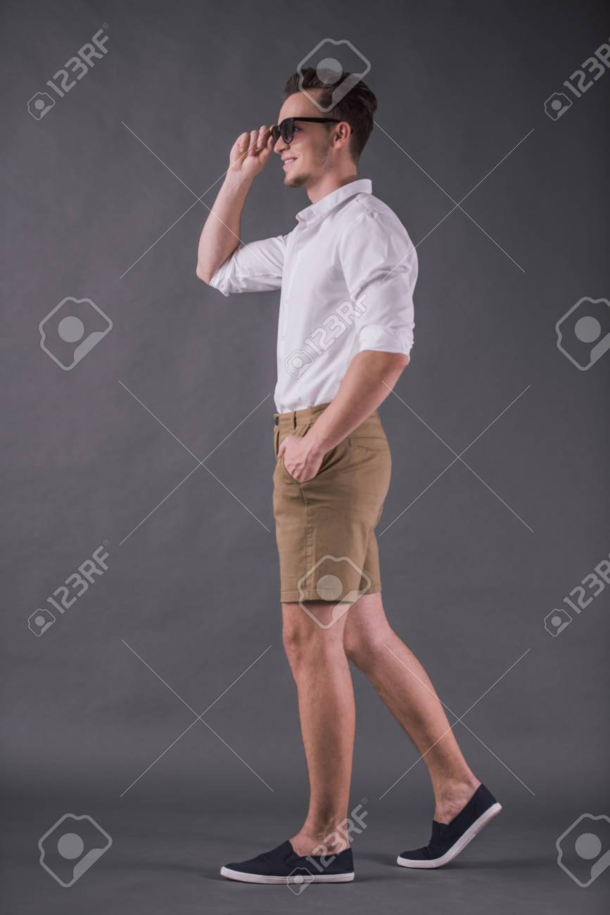 Full-length, back view image of handsome young man in shirt, shorts and sun glasses smiling while walking on gray background - 102395418