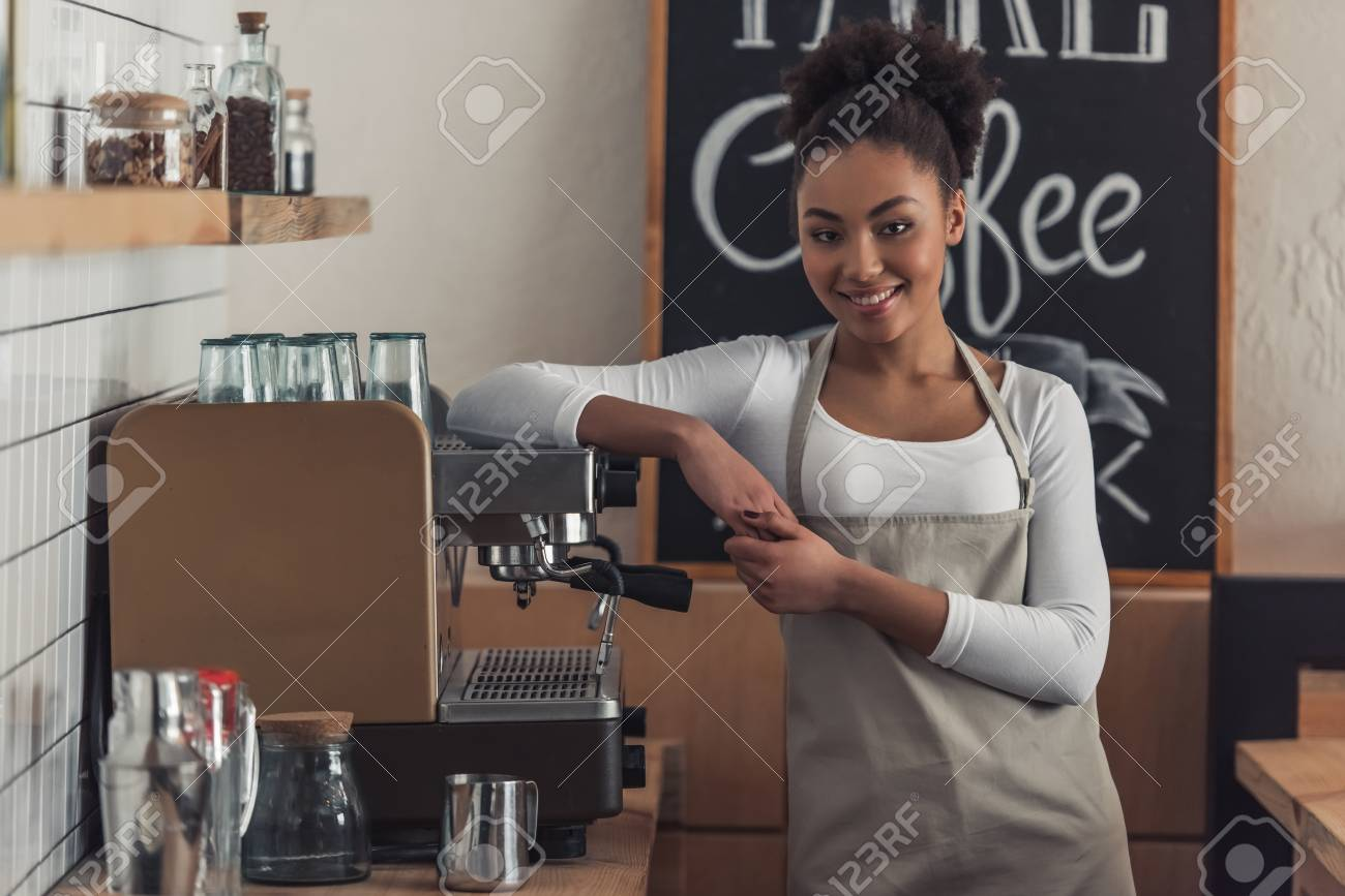 Beautiful Afro American barista in apron is looking at camera and smiling while leaning on the coffee machine - 107928401