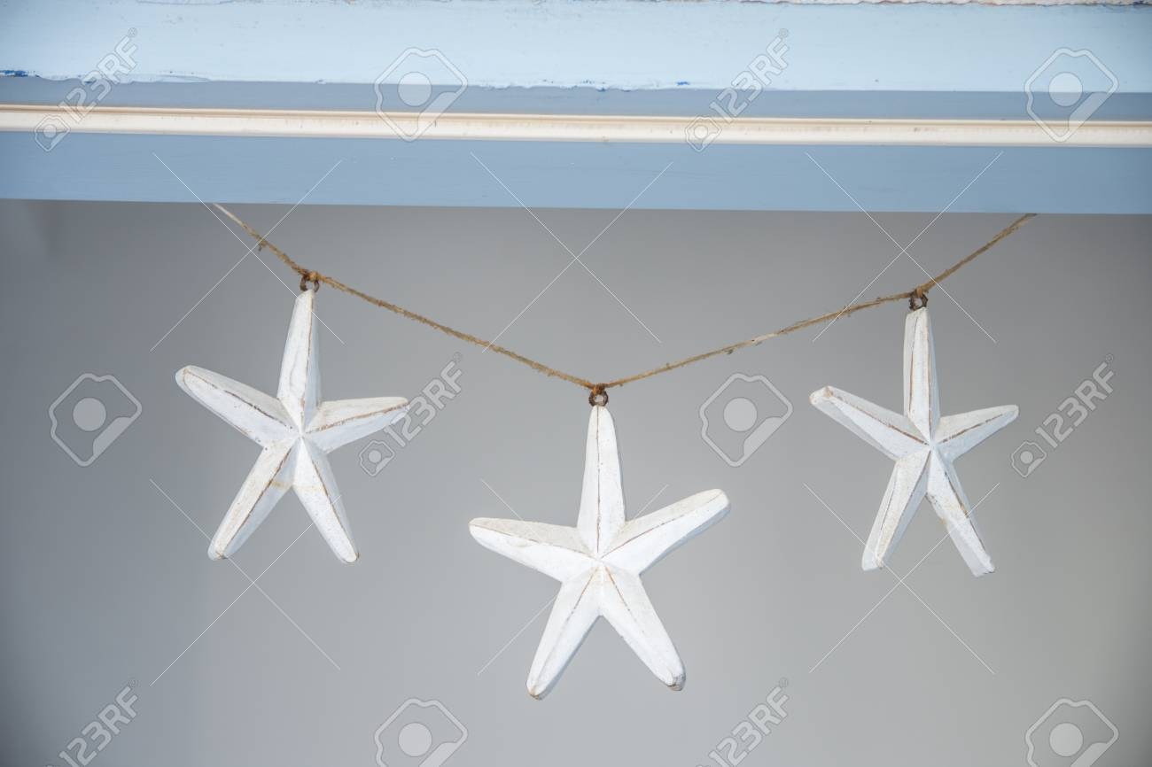 Three Small Wooden White Stars Hanging Over The Doorγg