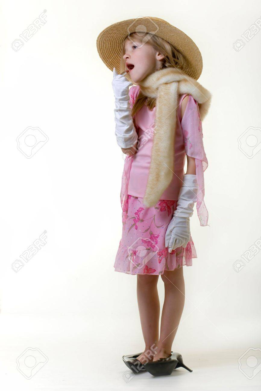 cute little eight year old girl wearing white gloves and too big high heeled shoes putting on lipstick Stock Photo - 702959