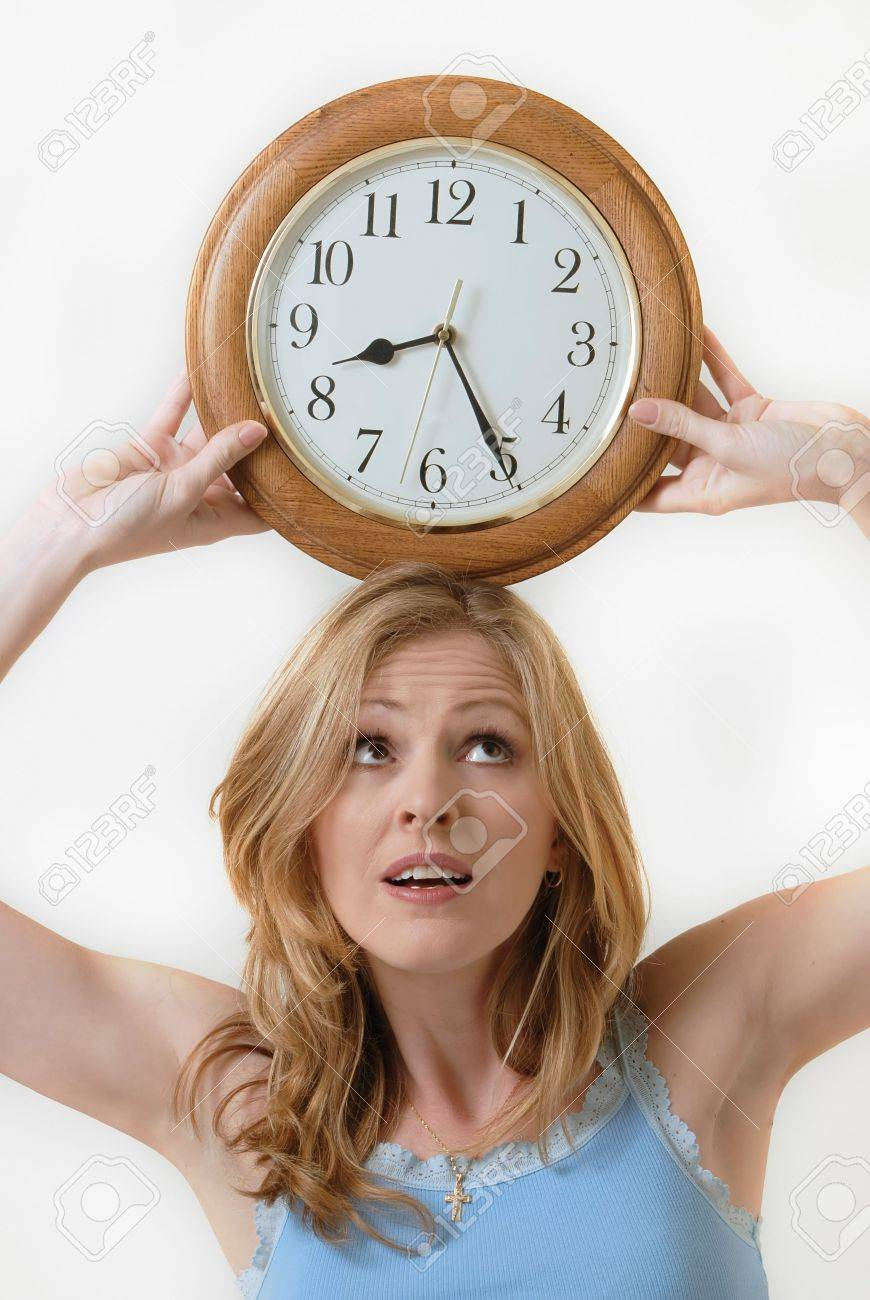 Attractive blond woman holding a round clock balanced on head at the time eight twenty-five showing time management Stock Photo - 808626