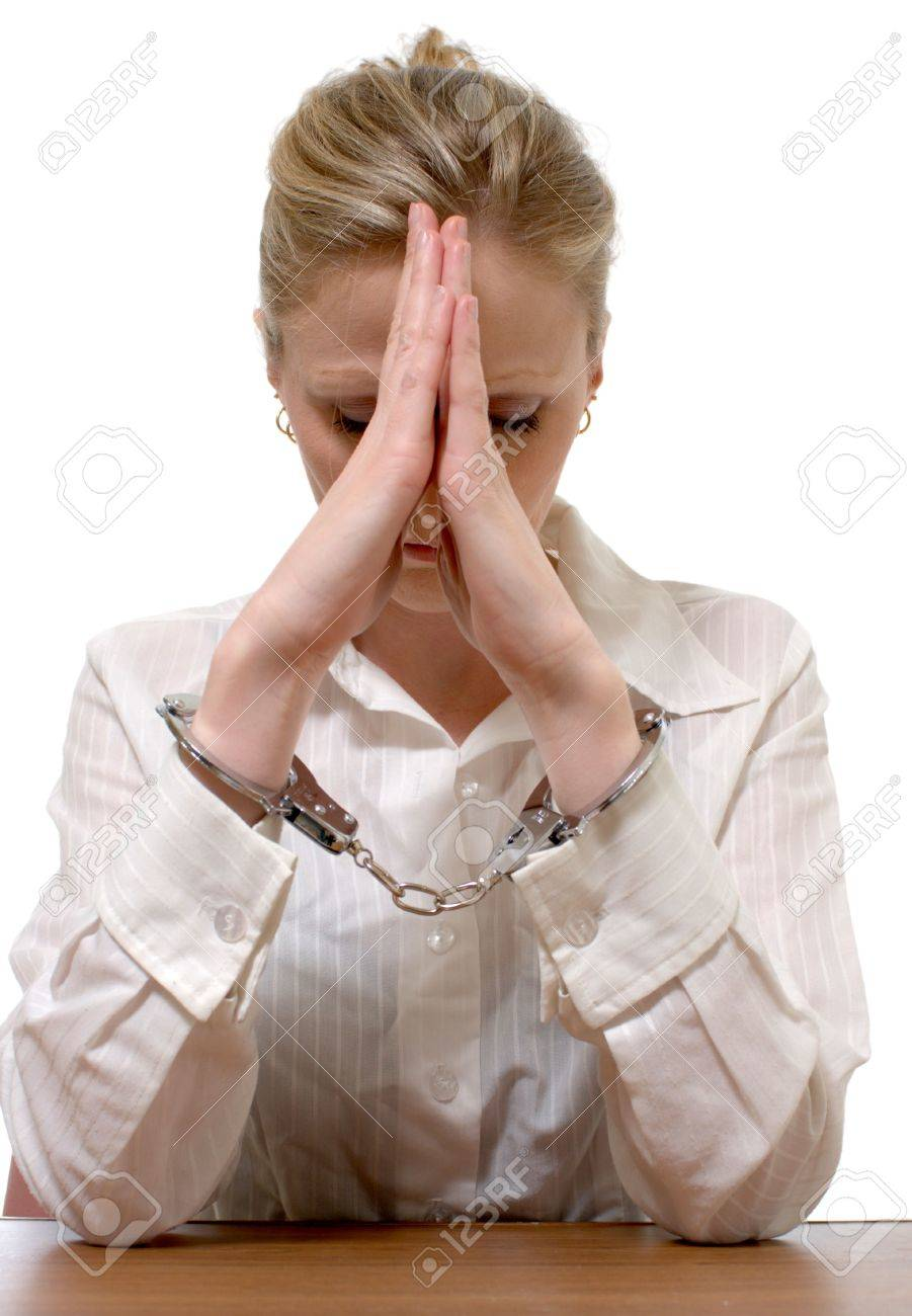Blonde professional looking woman wearing a white collared shirt with hands cuffed with elbows on table leaning on hands for the concept of white collared crime Stock Photo - 827710