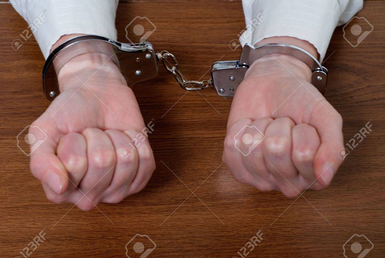 Pair of hands in fists on a wooden table top in handcuffs Stock Photo - 925090