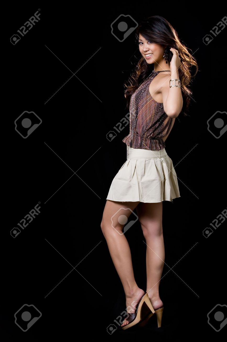 baff36f9b Full body of beautiful brunette Asian woman wearing mini skirt with blowing  backlit hair on black