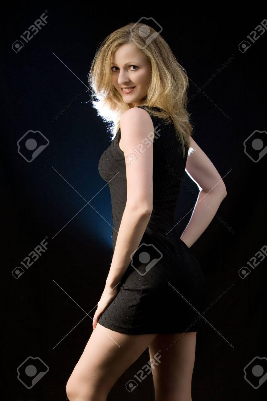 dd009d3ee380 Archivio Fotografico - Donna bionda bella dei capelli che porta vestito  sexy nero corto che propone sulla priorità bassa nera