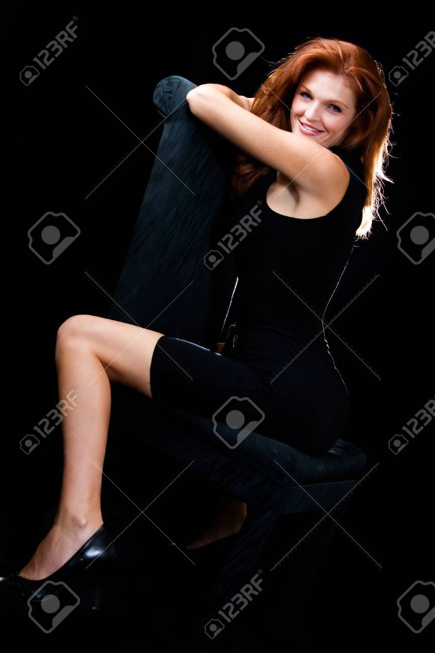 a79d7efade7e3 Stock photo whole body of a beautiful red hair woman in black sitting on a  black