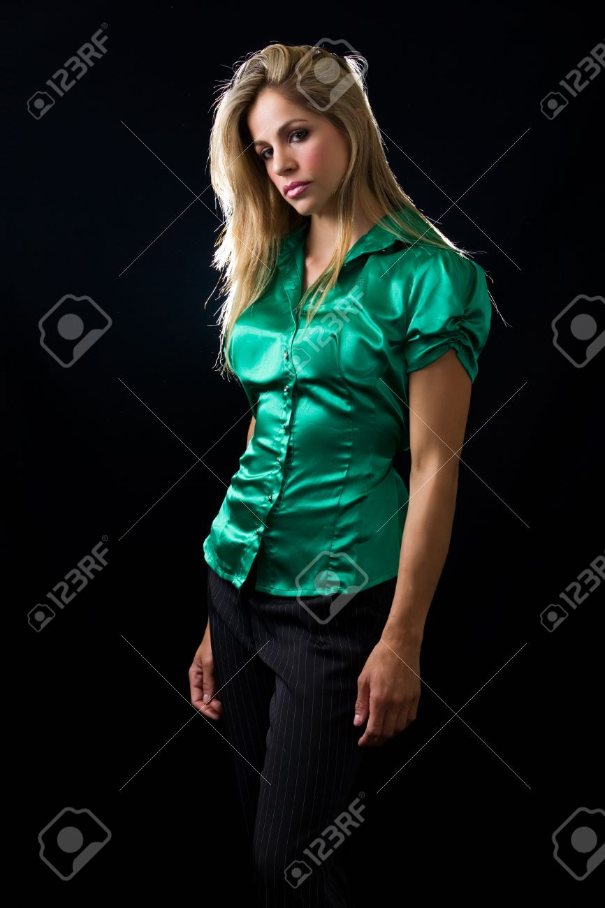 bbdf7b8f97a beautiful young woman with blond hair wearing shiny green satin blouse  posing on black background Stock