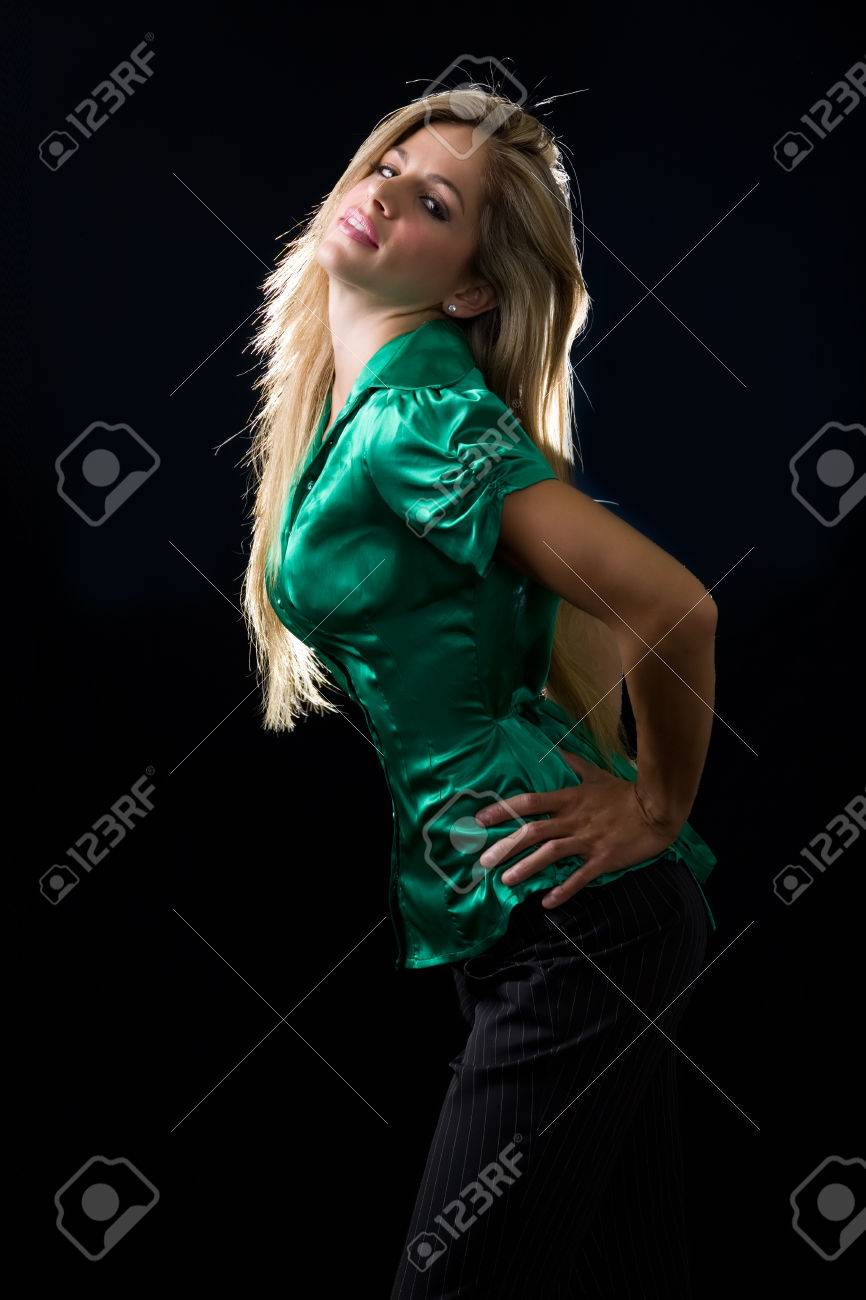 ace738eb4ff51 beautiful young woman with blond hair wearing shiny green satin blouse  posing on black background Stock