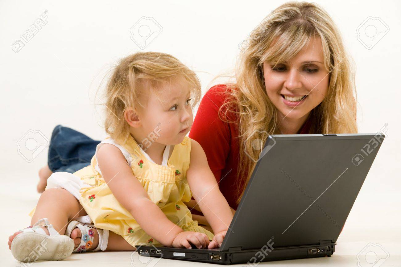 Adorable  girl toddler sitting on the floor with mom working on a laptop computer Stock Photo - 2073033