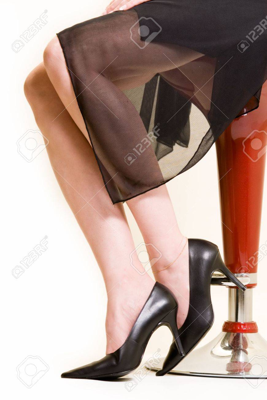 3cb05988ec74 Stock Photo - Woman s legs wearing black stiletto high heel shoes and  formal black see through dress sitting on a red stool