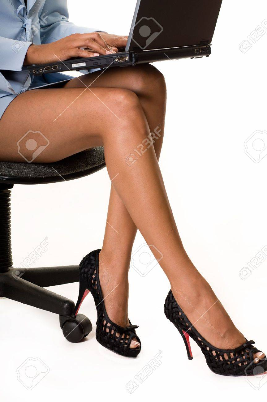 9255e749effd4d Legs of business woman sitting on a chair holding a laptop computer on her  lap Stock