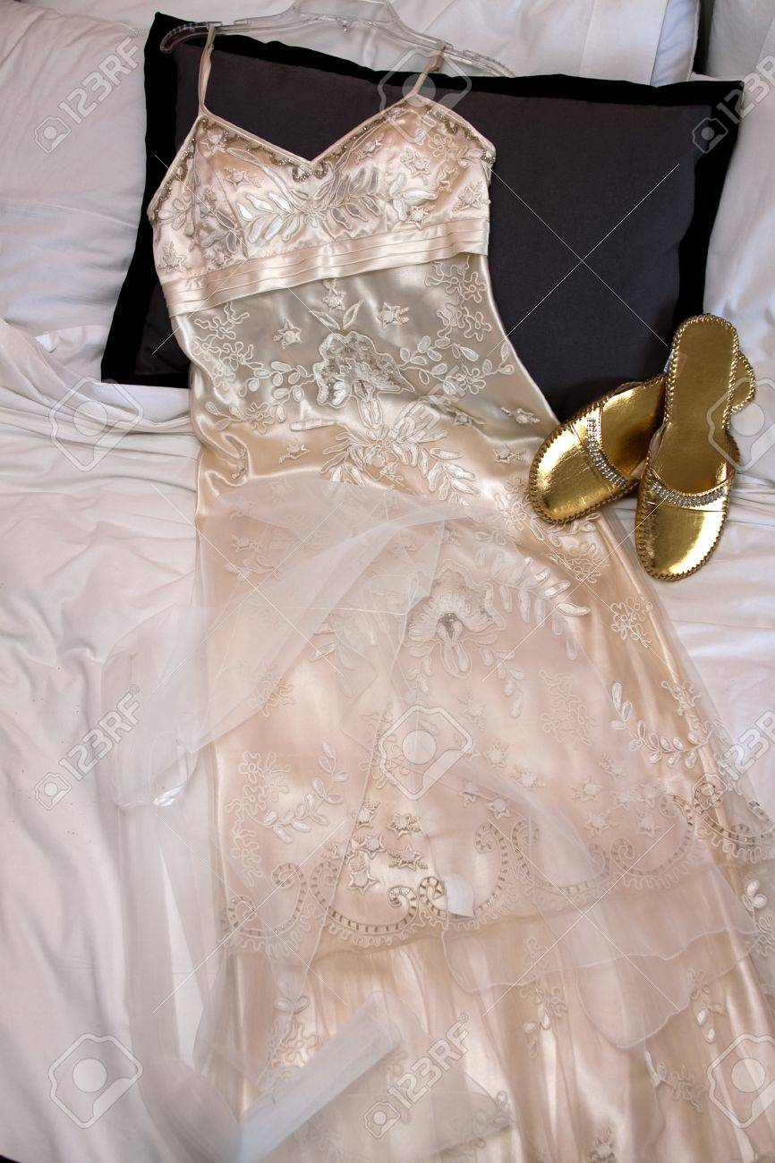 Woman\'s White Wedding Dress Laid Out Beside Gold Shoes On Bed Stock ...