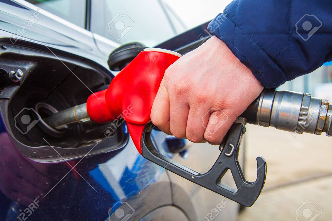 Fuelling gun inserted into the tank of blue car - 101559458
