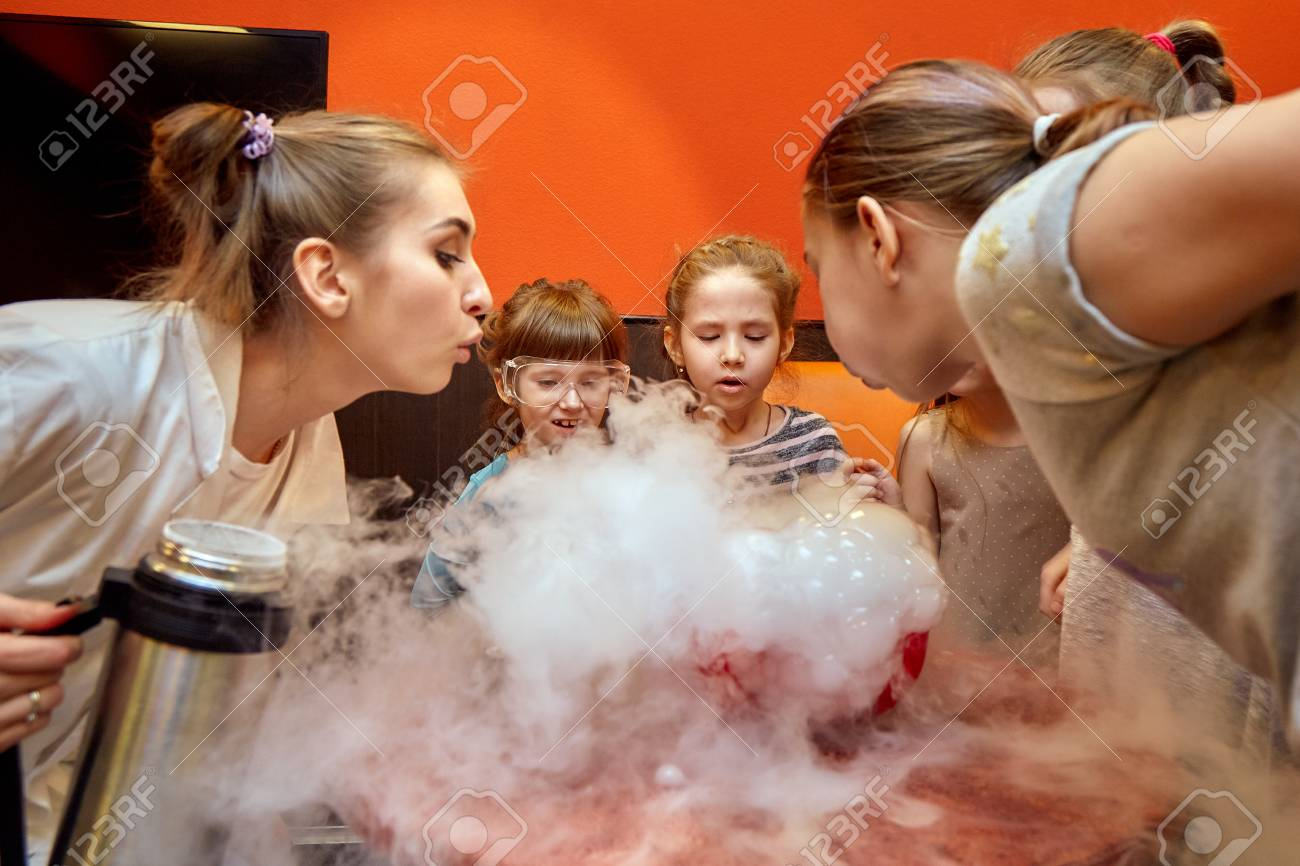 Chemical show for kids. Professor carried out chemical experiments with liquid nitrogen on Birthday little girl. - 121517389