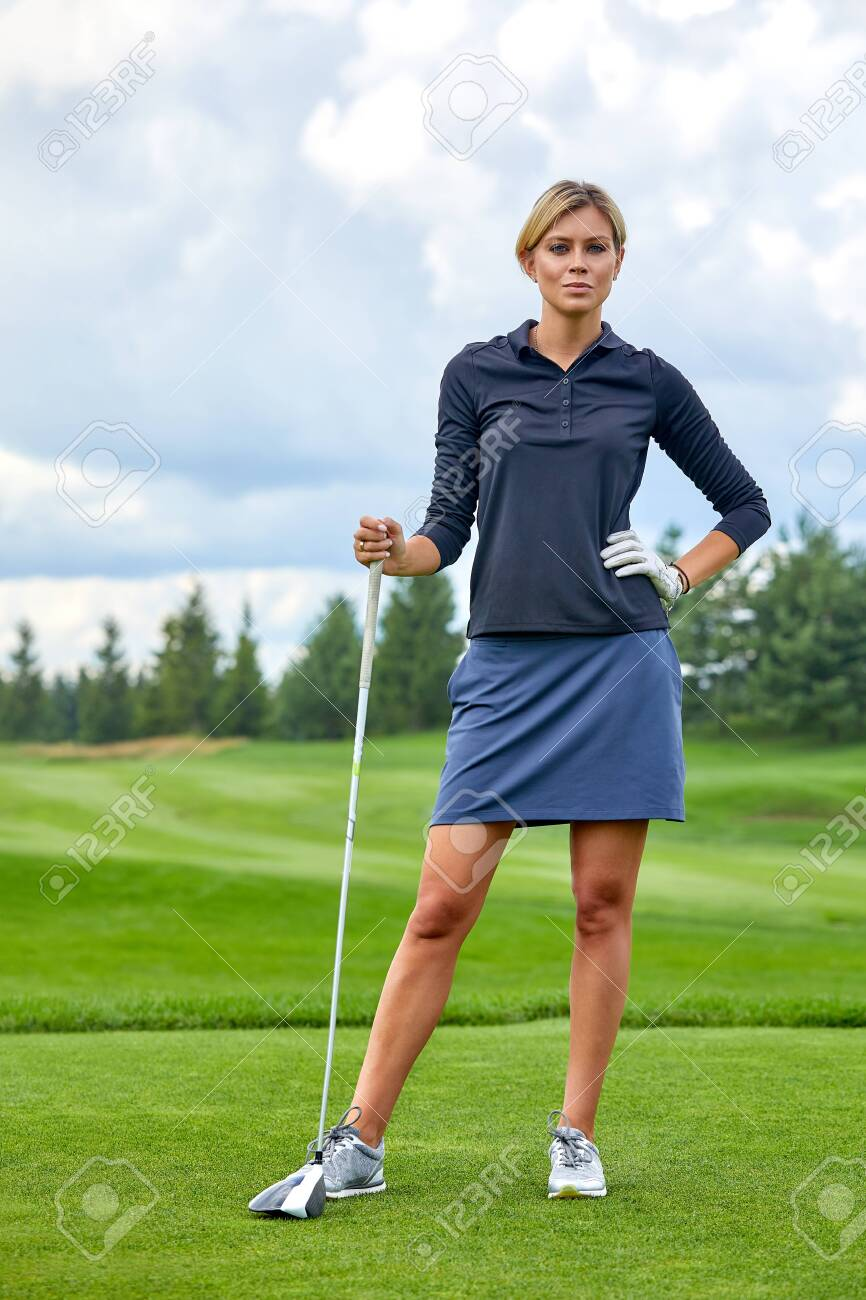 Portrait of a beautiful woman playing golf on a green field outdoors background. The concept of golf, the pursuit of excellence, personal excellence, royal sport. - 135368810