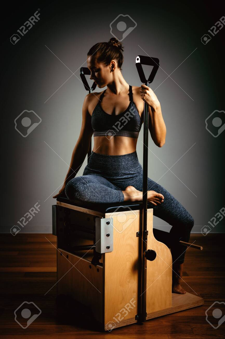 A young girl does Pilates exercises with a bed reformer, barrel machine tool. Beautiful slim fitness trainer on a background of a reformer gray, low key, light art. Fitness concept, healthy lifestyle. - 140514578