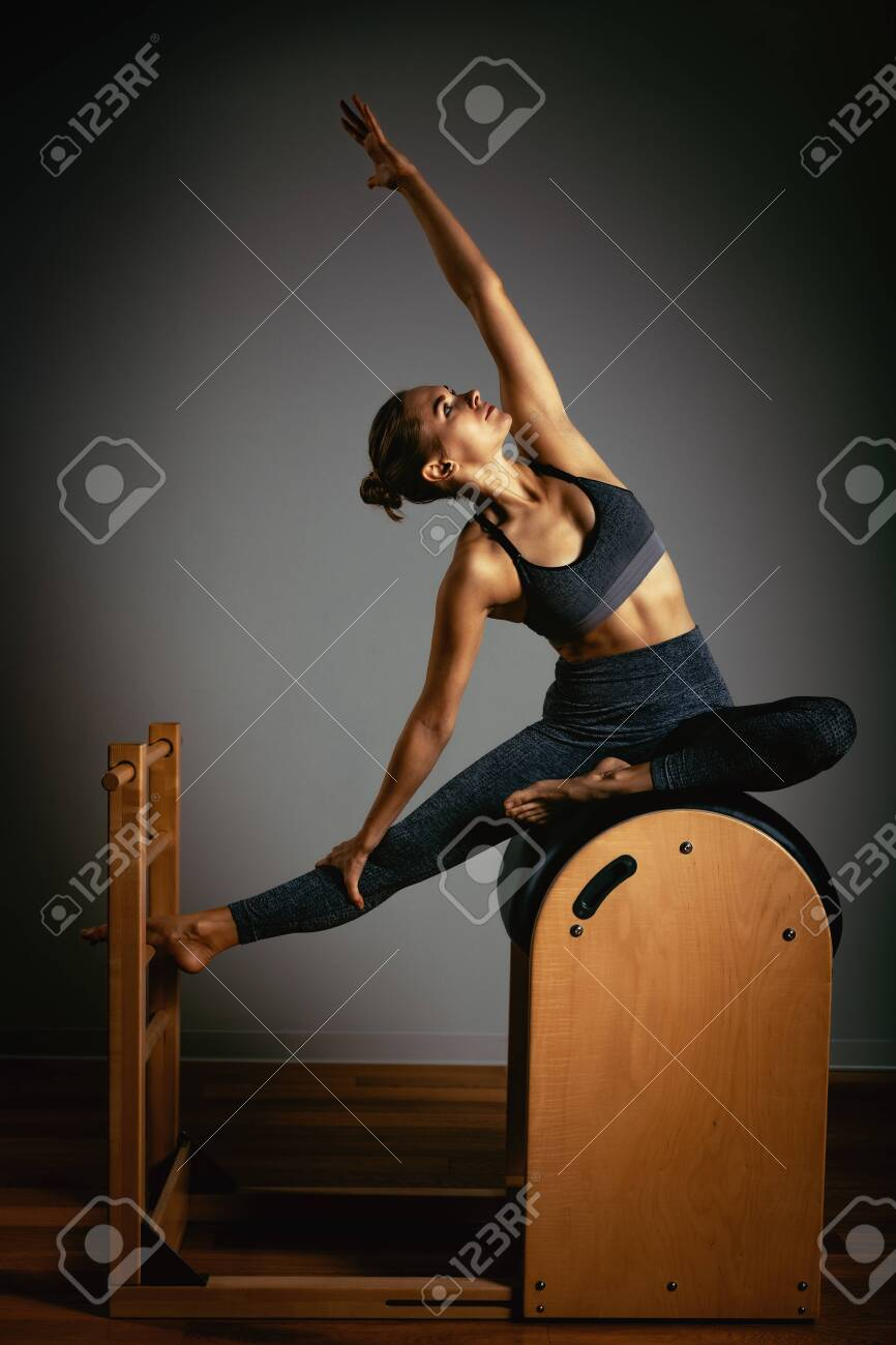 A young girl does Pilates exercises with a bed reformer, barrel machine tool. Beautiful slim fitness trainer on a background of a reformer gray, low key, light art. Fitness concept, healthy lifestyle - 140423982