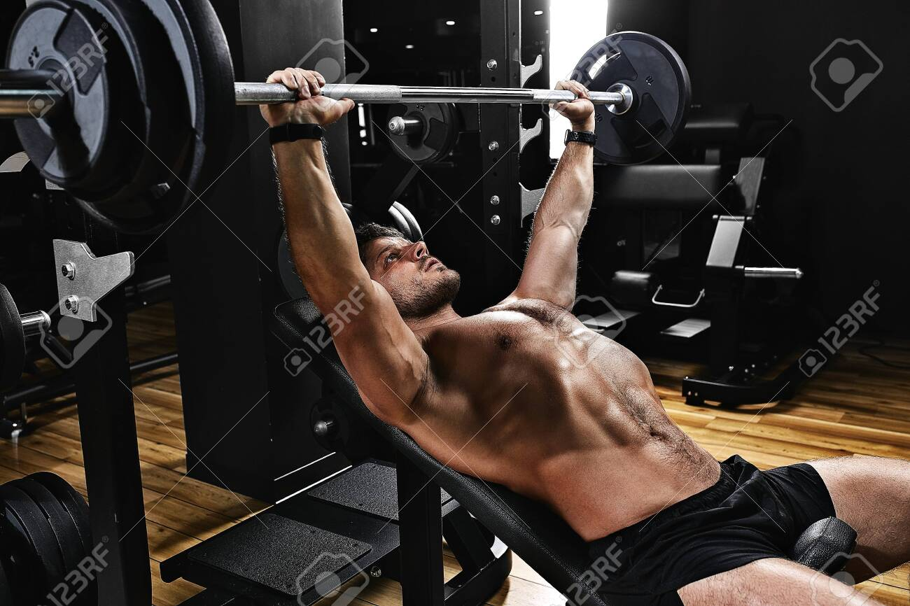 handsome young man doing bench press workout in gym, Fitness motivation, sports lifestyle, health, athletic body, body positive. Film grain, selective focus - 142606589