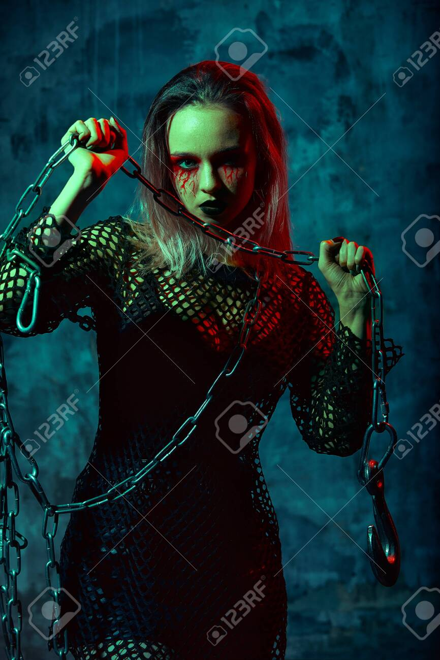 close up portrait of beautiful witch with halloween makeup. red and black face painting. chain in hands - 144880867