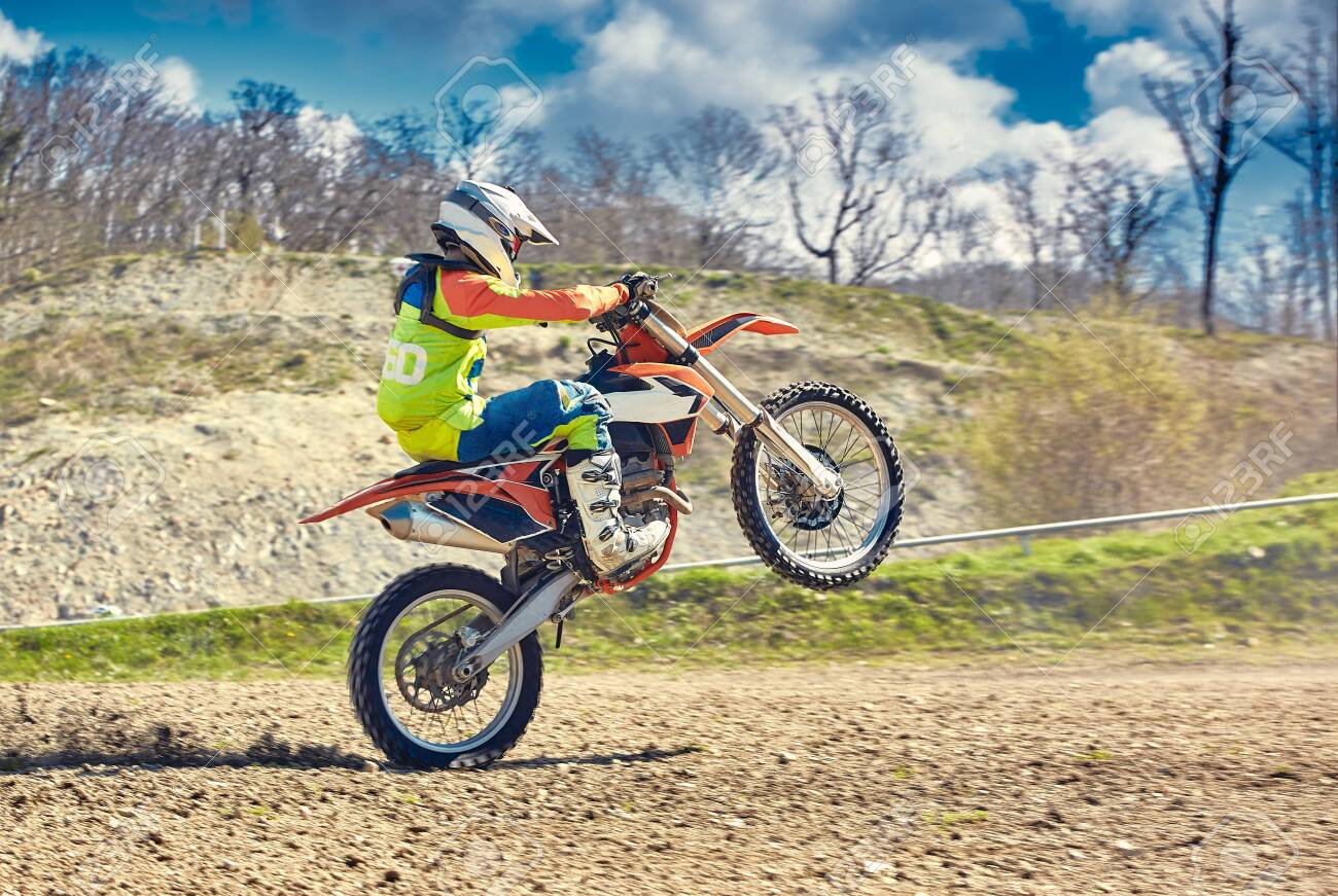 Motocross, a rider stands on the rear wheel of a bike, Riding on the rear wheel. Extreme, industrial, motorcycle cross-country riding for extreme - 147531792