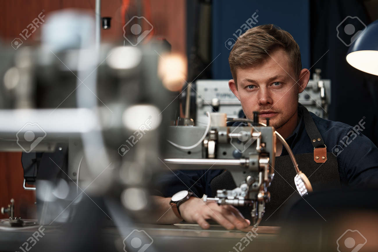 Working process of leather craftsman. Tanner or skinner sews leather on a special sewing machine, close up.worker sewing on the sewing machine - 166685967
