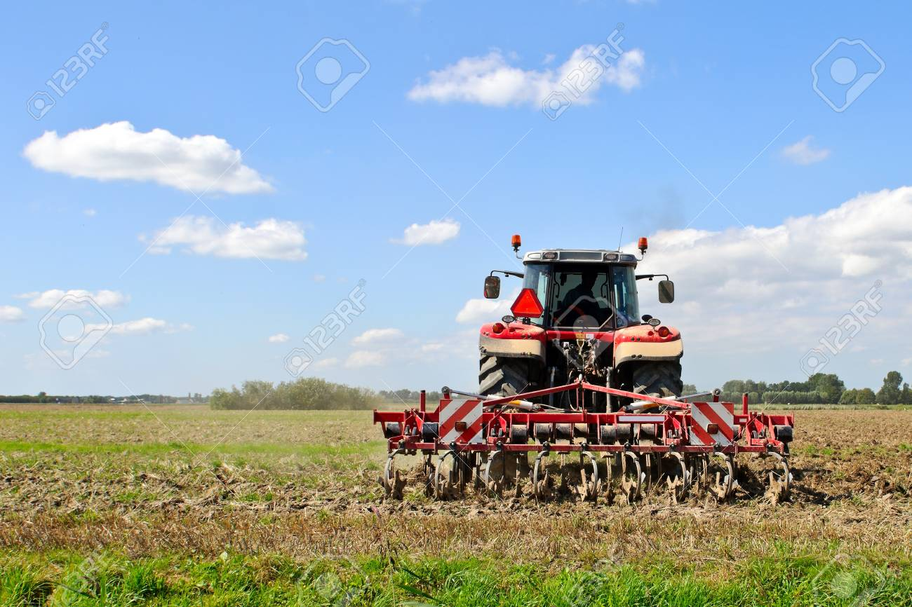 red tractor during cultivation with plough Stock Photo - 14115024