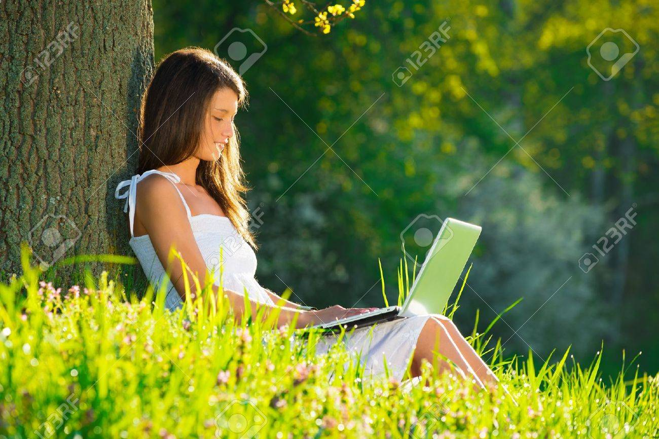 Beautiful young woman relaxing on grass with laptop - 19428711