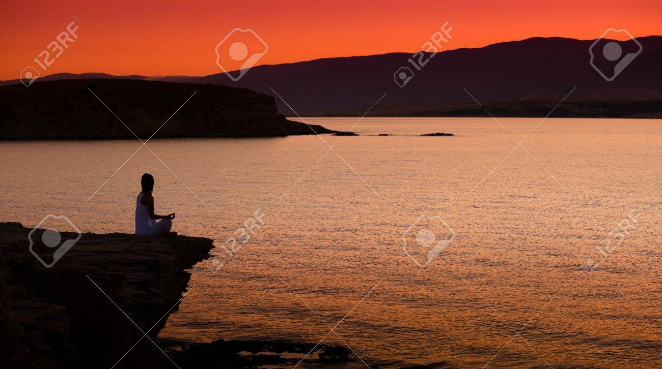 Silhouette of a woman doing yoga on the beach at sunset Stock Photo - 22101909