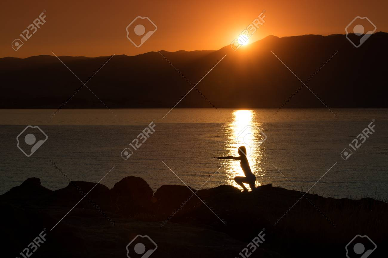 Silhouette of a woman doing yoga on the beach at sunset Stock Photo - 22101961