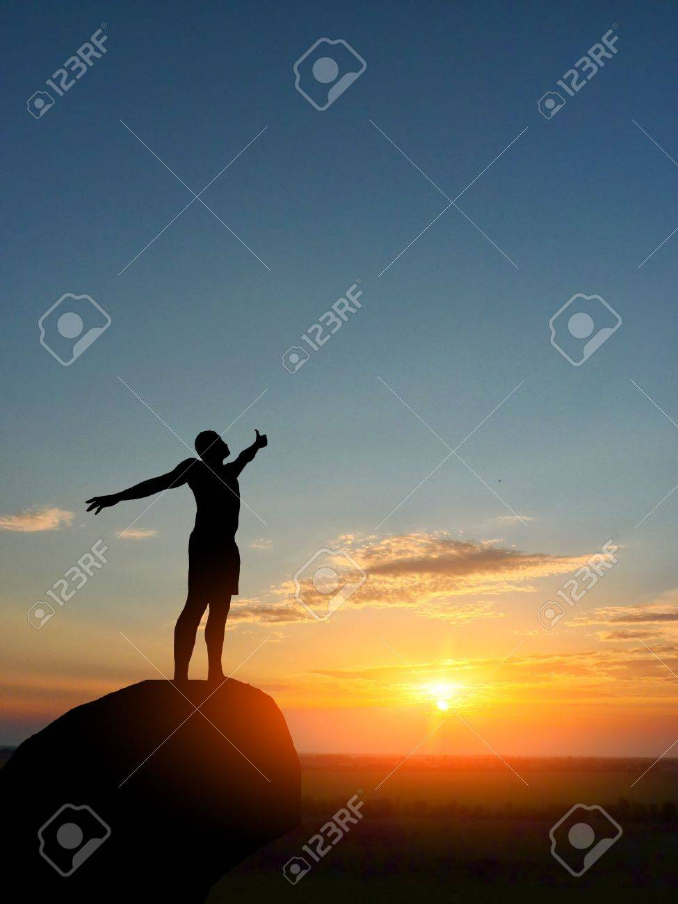 man on top of the mountain reaches for the sun - 10411141