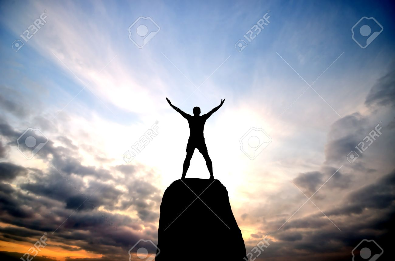 Man On Top Of The Mountain Reaches For The Sun Stock Photo ...