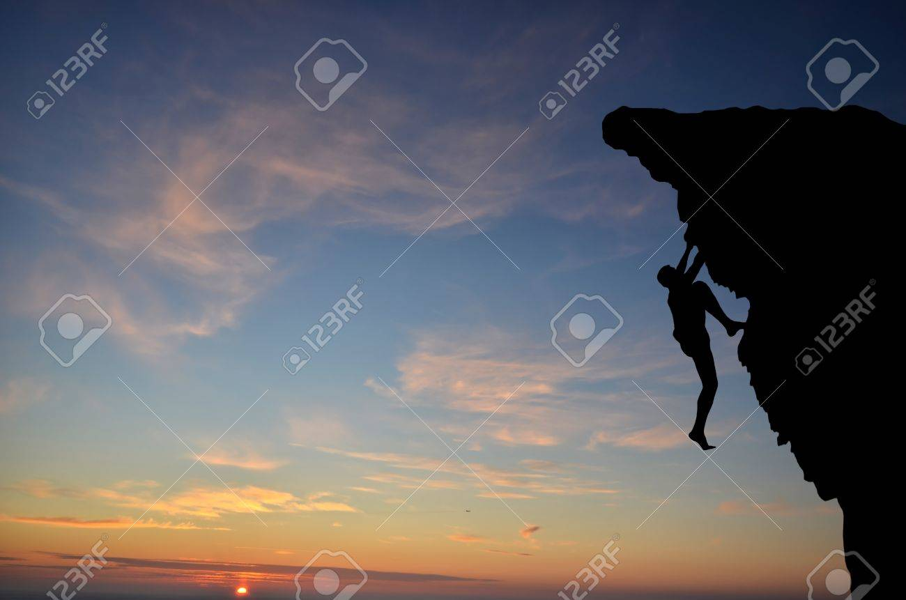 silhouette of a person without insurance climbs the rock in the background of the sunset - 12296307