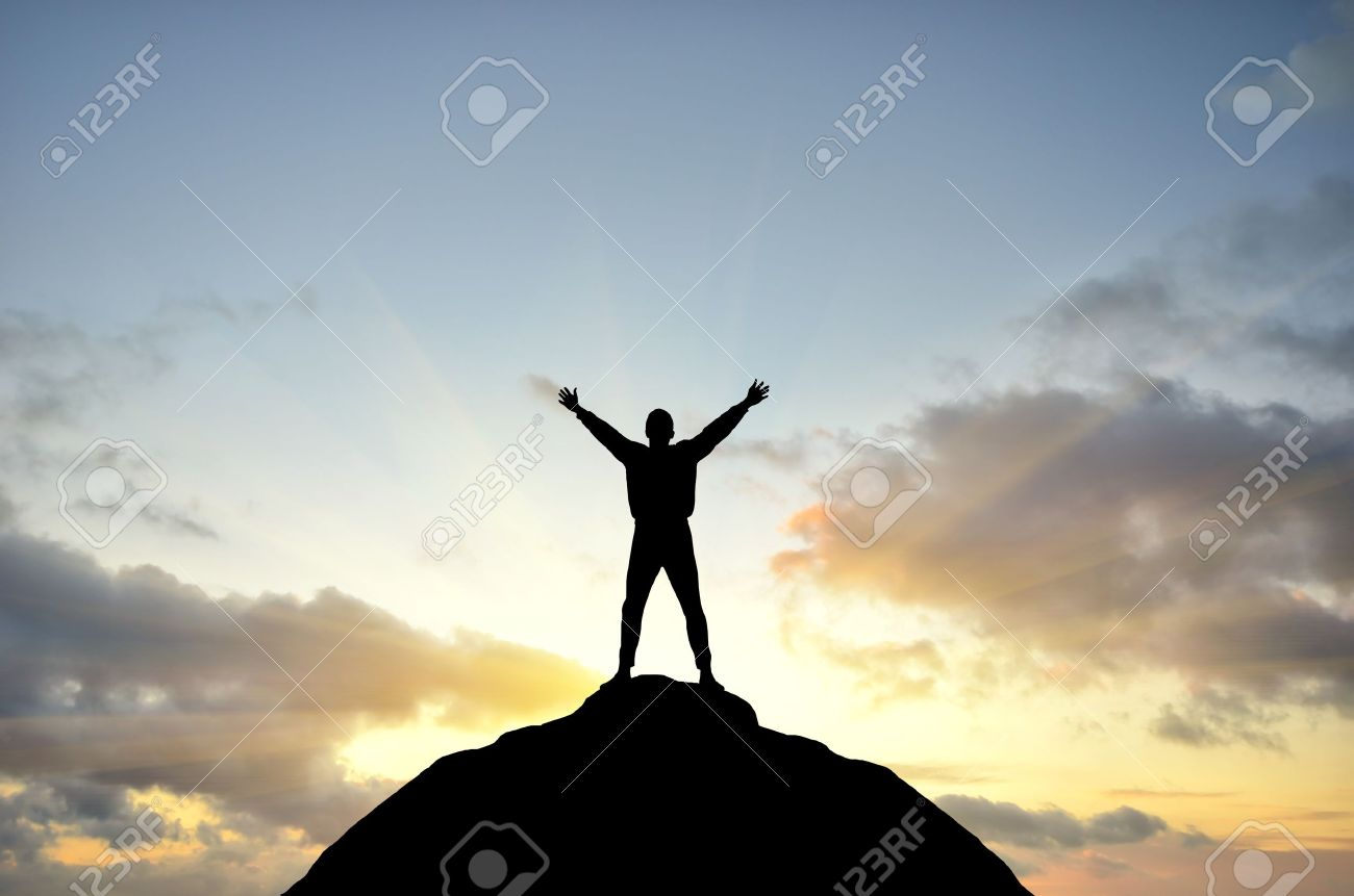 man on top of the mountain reaches for the sun - 12296263